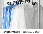 Small photo of Rack with clean shirts in laundry