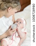 mom holding and giving milk... | Shutterstock . vector #1008728980