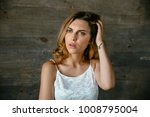 Small photo of Charming woman with brown eyes keep her head with hand, trying to remember something important. Dressed in white singlet.