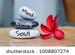 Small photo of Holistic health concept of zen stones with deep red plumeria flower on blurred background. Text body mind soul.