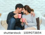Small photo of Happy Asian Lover kissing and hugging which holding a cup of water on the sofa in living room at modern home, Couple and life style concept
