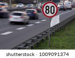 Small photo of Speed limit sign with a traffic in the background
