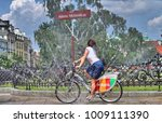 Small photo of Warsaw/Poland - June 26, 2016: Pretty young woman riding a Nextbike bicycle (city bike) with mBank logo through the water curtain on Adama Mickiewicza's square