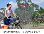 Small photo of Warsaw/Poland - June 26, 2016: Pretty smiling young brunette woman riding a Nextbike bicycle (city bike) with mBank logo through the water curtain on Adama Mickiewicza's square