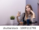 Small photo of A beautiful young woman sits at a table with a mug of tea and a biscuit with a very sad and sad face and holds in her hand a phone, a rustle, resentment, a bad mood. Internet trolling.