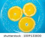 sliced orange in blue soda... | Shutterstock . vector #1009133830