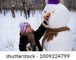 a small cheerful girl holds a... | Shutterstock . vector #1009224799