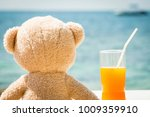 teddy bear looking out to sea... | Shutterstock . vector #1009359910