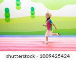 child jumping on colorful... | Shutterstock . vector #1009425424