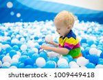 child playing in ball pit.... | Shutterstock . vector #1009449418