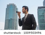 Small photo of Young businessman talking on the cellphone in a city street