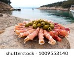 Prosciutto with green olives on the plate in the bay. A small lunch break when curising. Croatia
