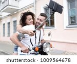 happy couple on scooter making... | Shutterstock . vector #1009564678