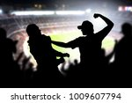 Small photo of Fight in a football game crowd. Angry man hitting another spectator in soccer match audience. Violent argument between two fans of different teams and clubs. Hooligans and violence in sport event.