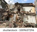 Small photo of Demolish building with debris in city, broken house on ruin demolishing site after destruction