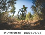 Wide angle view of a mountain biker speeding downhill on a mountain bike track in the woods - stock photo