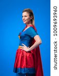 Small photo of side view of beautiful woman in superhero costume standing akimbo isolated on blue