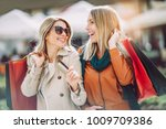 Happy friends shopping. Two beautiful young women enjoying shopp
