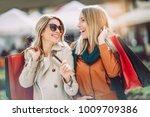 Happy friends shopping. Two beautiful young women enjoying shopp