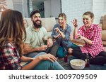 Small photo of Happy friends playing game guess who and having fun at home