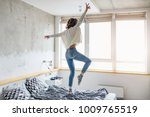 young happy woman jumping on... | Shutterstock . vector #1009765519