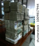 Small photo of Blurry stack of Myanmar Kyat money on a wooden table, defocused financial background, foreign currency and trade concept