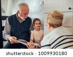 elderly couple showing a photo... | Shutterstock . vector #1009930180