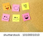 Small photo of office post it notes with various smiley happy faces on cardboard with copy space