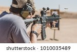 Man shooting rifle on desert...