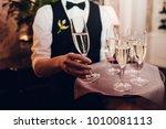 waiter brings glasses of... | Shutterstock . vector #1010081113