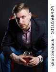 Small photo of Male alcoholism, man with a glass of alcohol in hand. Disease of alcoholic addiction, bad habit, stress relief through alcohol. Anonymous alcoholic