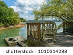 Small photo of Blue Ridge, Tennessee, USA. Rustic rocking chair on wooden deck under shade of tree on bank of lake in Smoking mountains in summer near Blue Ridge, Tennessee, USA.