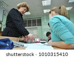 Small photo of Gadjievo, Russia - January 19, 2011: The teacher conducts laboratory work in physics in physics