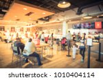 Small photo of Blur modern hipster open coffee shop, self-serve bakeries in USA. Long people sit and stand queuing behind stanchion barriers check-out counter. Wall mount led menu board digital signage. Vintage tone