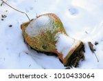 broken clay jug in the snow.... | Shutterstock . vector #1010433064