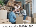 happy family unpacking... | Shutterstock . vector #1010441980