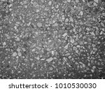 Small photo of Dark background. Inhomogeneous texture. Gray polished concrete with white stones. An evenly poured solution of crushed stone, cement and sand.