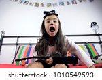 little girl playing on ukulele  | Shutterstock . vector #1010549593