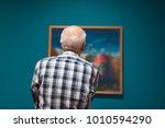 Senior Man Admiring Artwork In...
