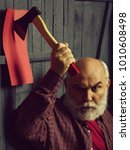 Small photo of Senior man. Old man with white beard holding axe on red paper in wooden wall