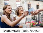 payment, finances and people concept - smiling young women paying for coffee with cash money at street cafe - stock photo