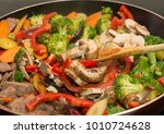 Small photo of Side view of wooden spoon stirring beef and vegetables in cast iron skillet - Stir frying
