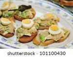 closeup of a pile of bread slices topped with boiled egg served as tapas - stock photo