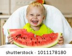 happy baby eating a slice of a... | Shutterstock . vector #1011178180