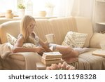 young woman reading book at home | Shutterstock . vector #1011198328