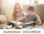 brother and sister reading a... | Shutterstock . vector #1011198334