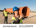 couple transports a plastic construction pipe working as a team - stock photo