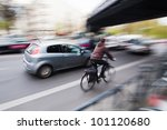 city traffic with a cyclist and cars in motion blur - stock photo