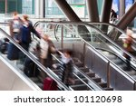 rail station with people in motion blur on the escalator - stock photo