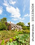 Small photo of STRATFORD UPON AVON, ENGLAND - AUGUST 9, 2012: Anne Hathaway's (William Shakespeare's wife) famous thatched cottage and garden at Shottery, just outside Stratford upon Avon, England.